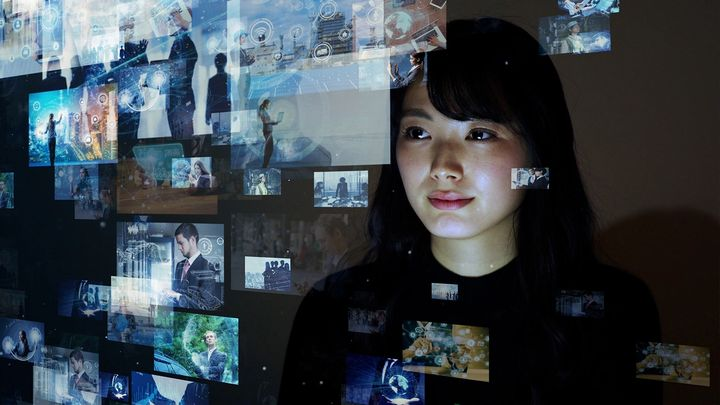 Asian woman viewing many screens of information floating in front of her
