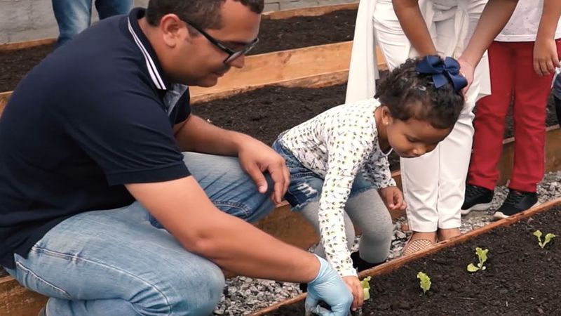 Man and young girl planting lettuce plants in our onsite garden at Pouso Alegre, Brazil.