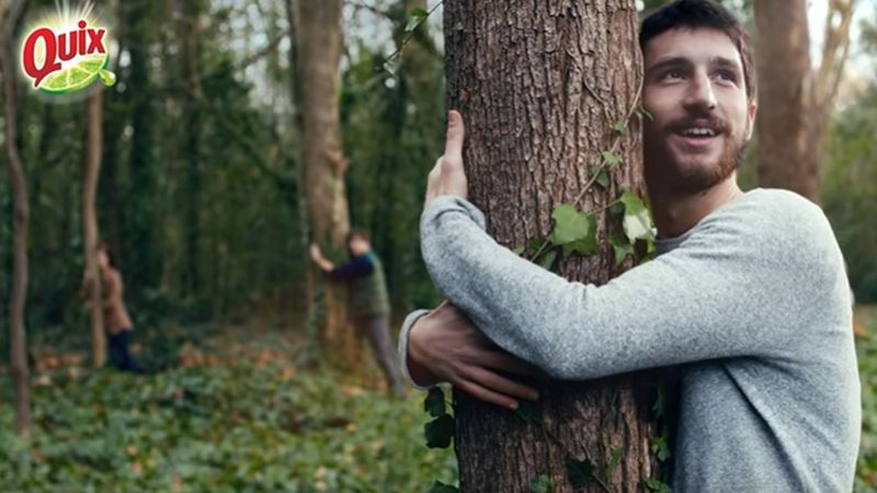 A static shot from a Quix television advert. The photograph features a man hugging a tree.