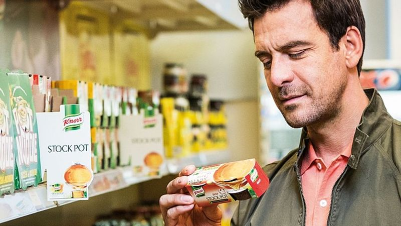 A man looking at the nutrition label on a Knorr product