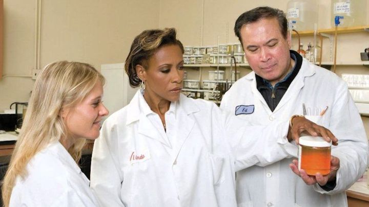 Three people in white lab coats standing in a science lab look closely at a small jar full of a chemical substance.