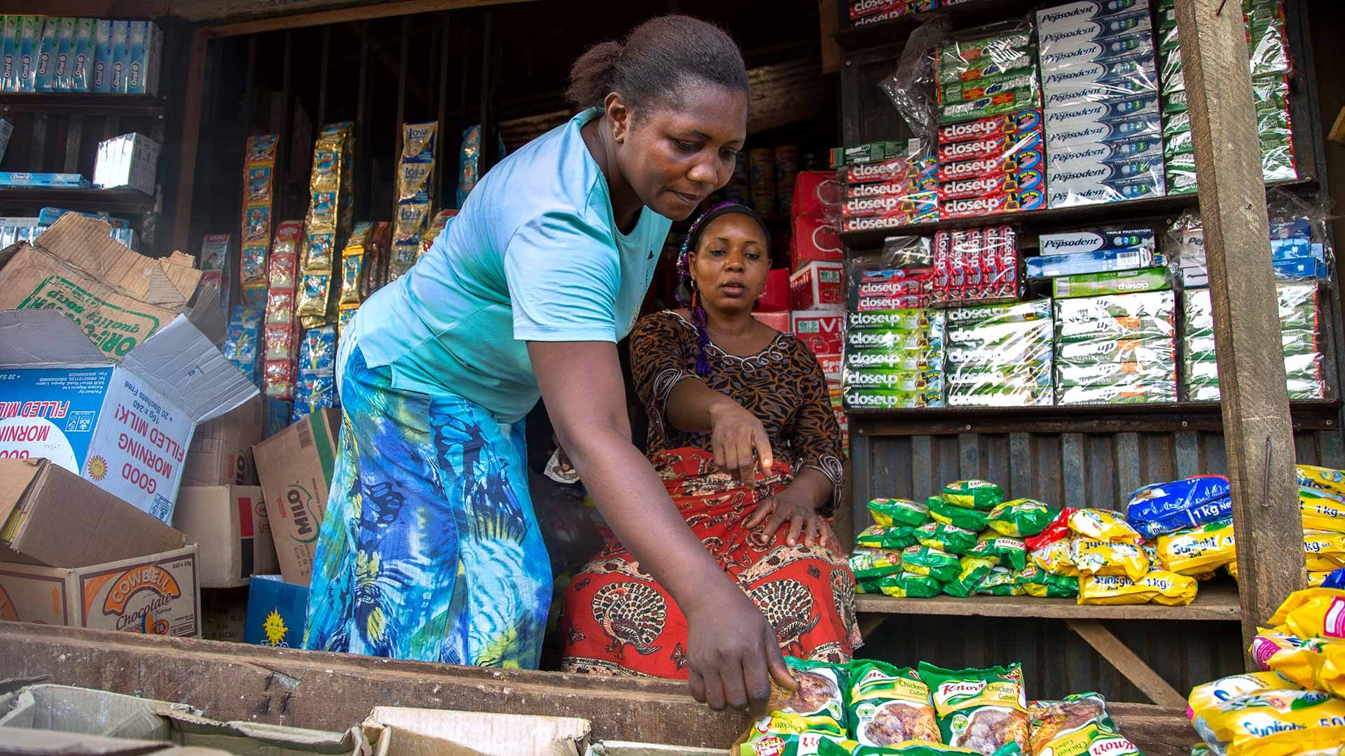 Two women choose Knorr products from a Nigerian market stall