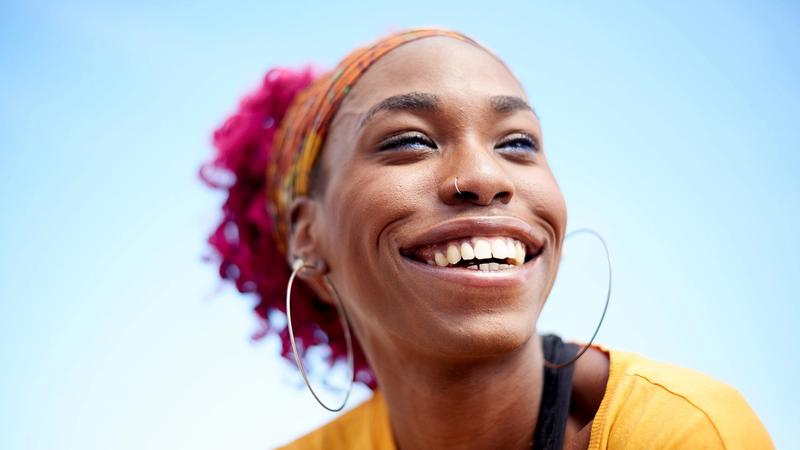 Young woman smiling against a blue sky
