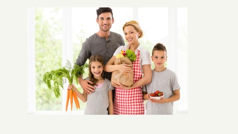 Family of mother and father with two children holding bag of groceries with fruits & vegetables