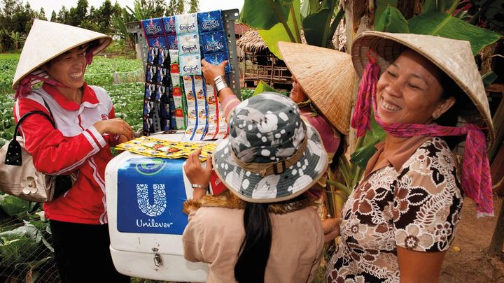 Women by a Market stall in Asia displaying Unilever products
