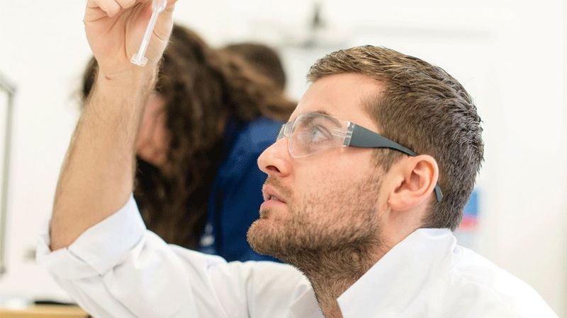 Scientist looking at a sample in a test tube
