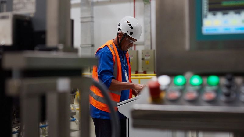 A man in a hard hat and high visibility waistcoat studies a dashboard in a factory