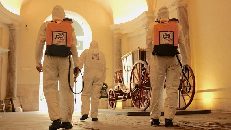 Three cleaners wearing protective clothing and carrying Lysoform spray backpacks in one of Italy's main museums.