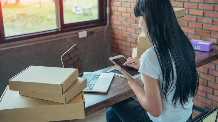 Asian woman at home online shopping. A laptop, an iPad and parcels surround her