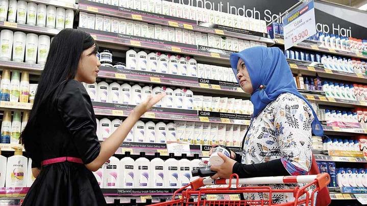 Consumenten die de producten van Clear in een kruidenier in Indonesië bespreken.