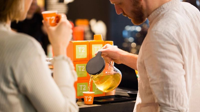 A photograph of two people drinking T2 tea together.