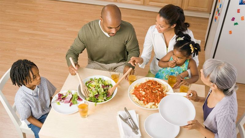 Mother & father serving two children dinner at table.