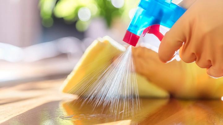 Close up of a cleaning product being sprayed and wiped down on a kitchen surface