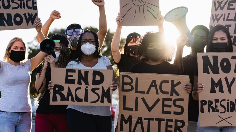 A group of demonstrators hold up posters calling for an end to racism