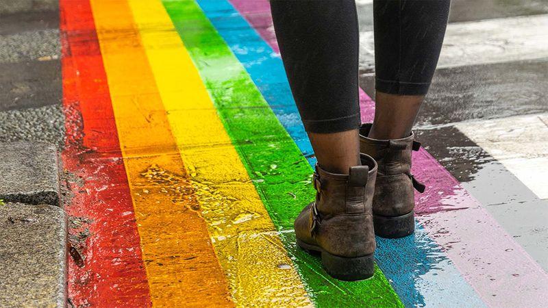 View of legs walking over a Gay Pride zebra crossing