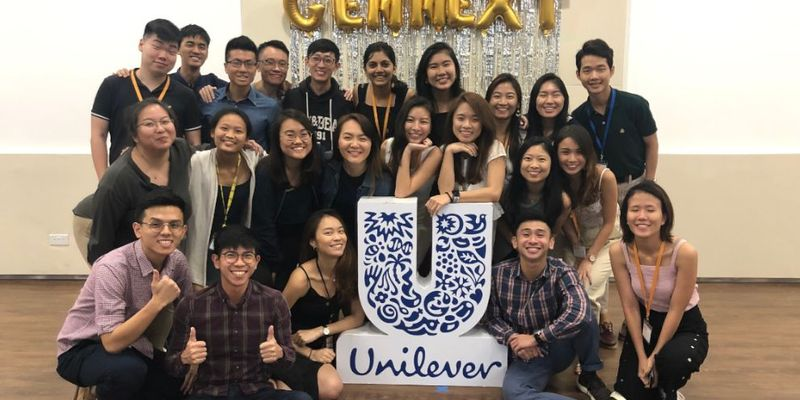 A group of smiling GEN-NEXT interns pose for the camera around a Unilever logo / --