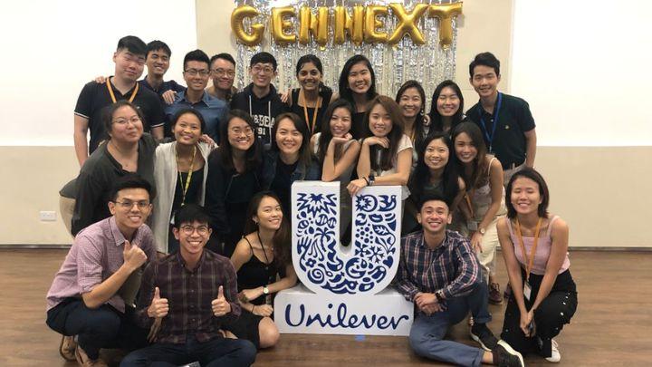 A group of smiling GEN-NEXT interns pose for the camera around a Unilever logo