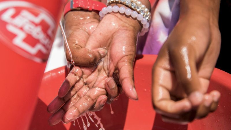 Hands washing under tap provided by Lifebuoy in a less economically developed country