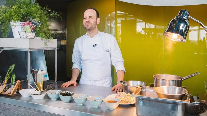 Michelin-starred chef Gregory Marchand stands behind a kitchen worktop bowls of a variety of ingredients