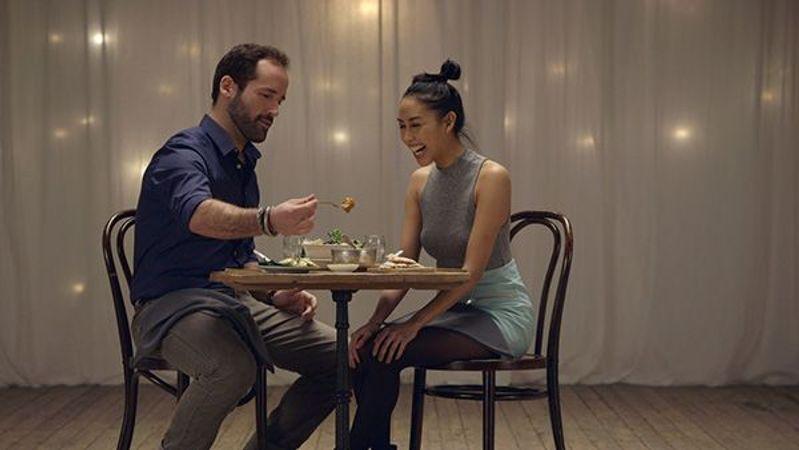 Asian woman and Caucasian man with beard in early thirties having dinner and laughing.