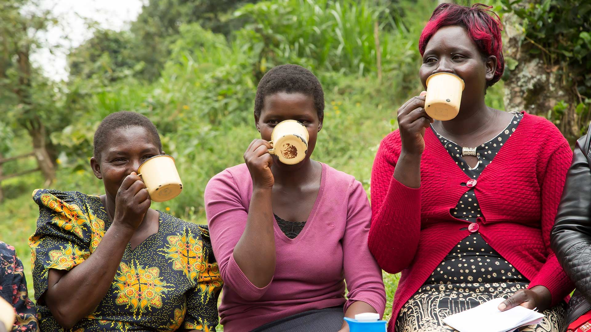 Three women drink tea from tin mugs during a break in a farmer field school training session