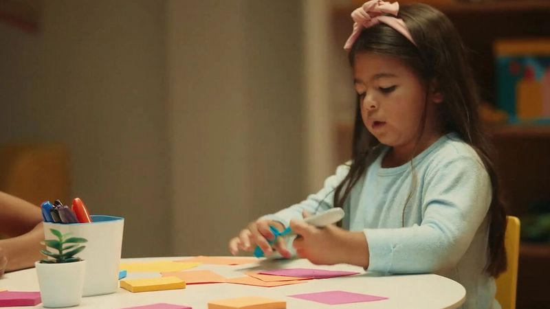 A photograph of a child writing something on a piece of paper.