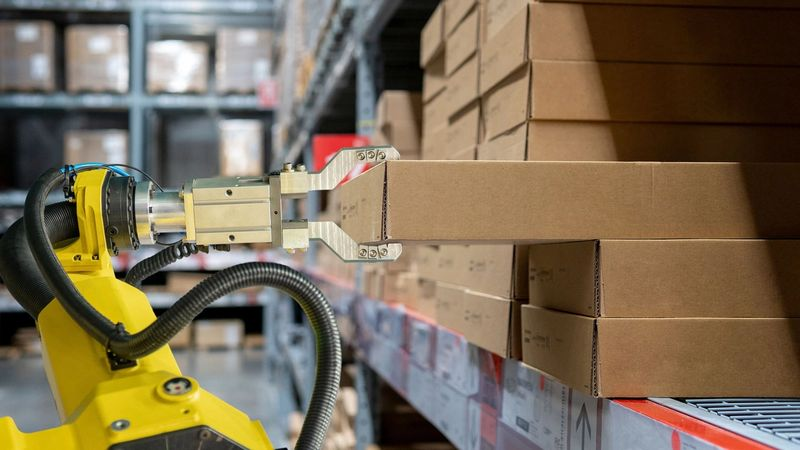 A robotic arm selects a cardboard package from a stack in a warehouse