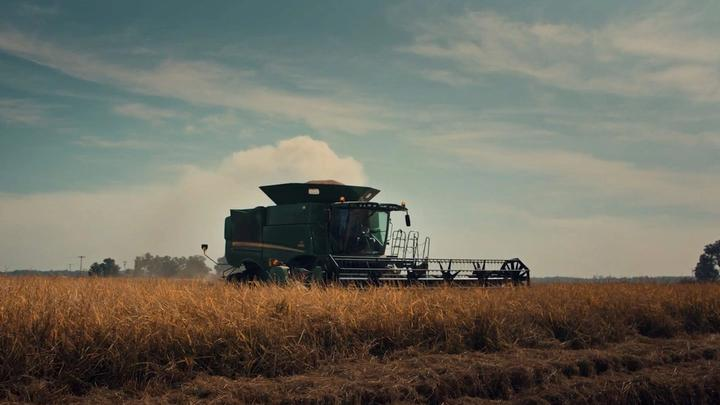 A tractor in a field harvesting crops