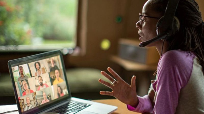 A woman speaks on a laptop to an online panel of people from diverse backgrounds