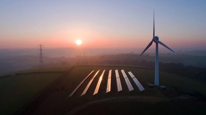 Aerial view of rural landscape showing wind turbine and solar panels in field.