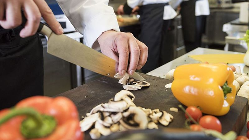 Image of chef in a kitchen cutting up vegetables