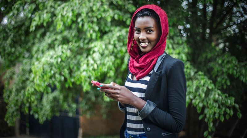 Woman holding mobile phone to make use of the Kasha mobile e-commerce platform in Rwanda