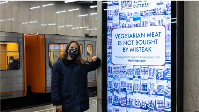 """""""Woman in a face mask in an underground station leaning against a Vegetarian Butcher billboard"""""""