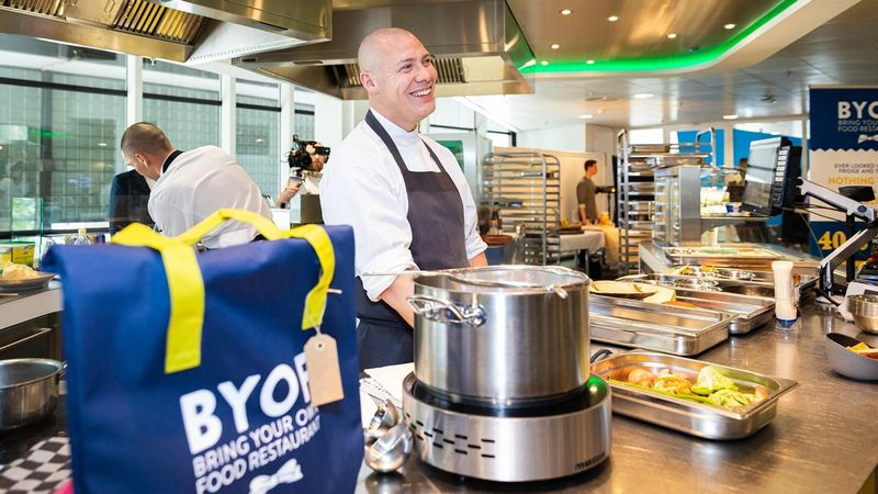 Chef in a kitchen with a Hellmann's 'Bring Your Own Food' restaurant bag