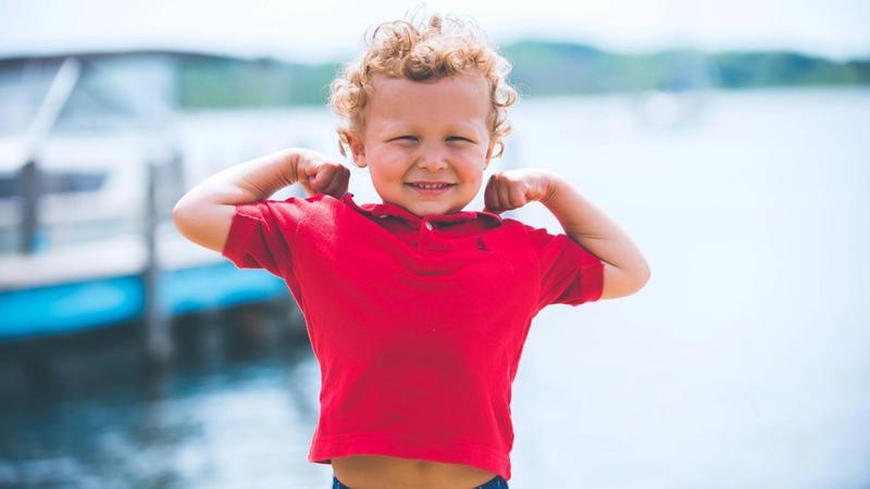 Boy in red flexing muscles