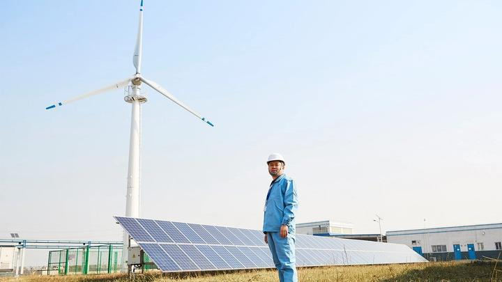 Worker in front of solar panels and wind turbine