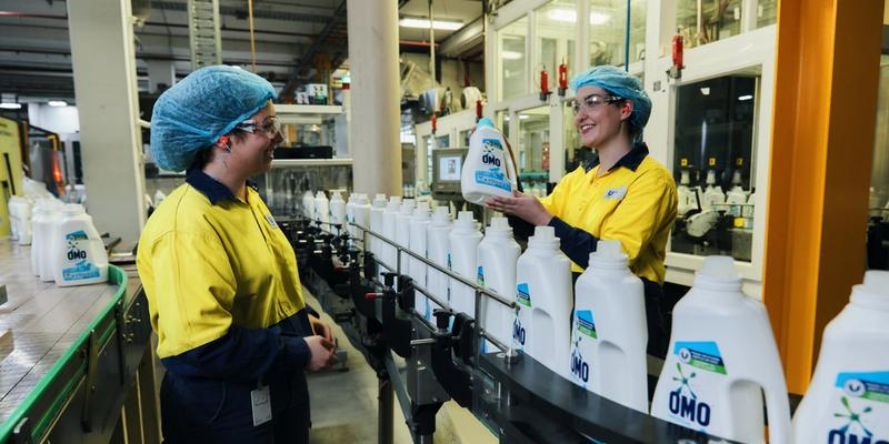 Factory workers standing over a line producing Omo liquid detergent