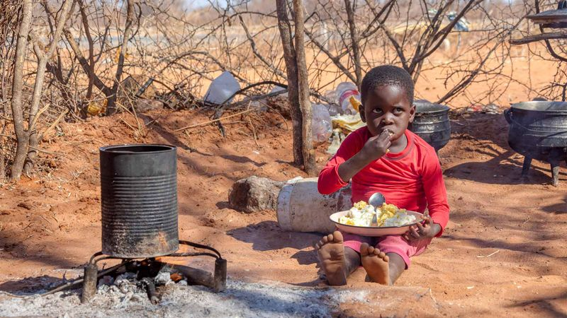 Toddler sitting on ground in African desert with a bowl of food