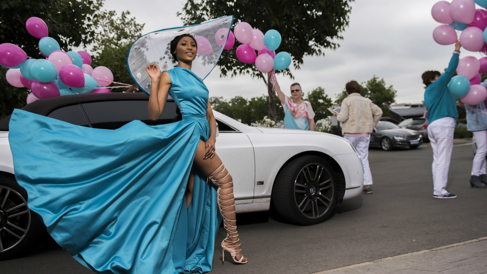 Woman with blue dress standing in front of a car
