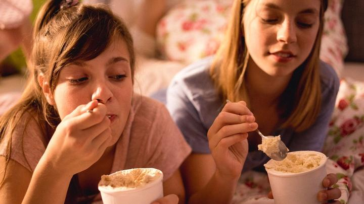 Two teenage girls lie on a bed eating big tubs of ice cream