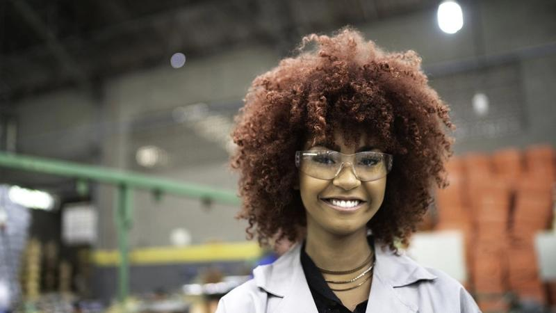 Young woman in lab coat and goggles. Unilever is committed to upskilling young people for 'future fit' job opportunities