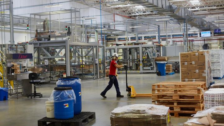 A person wearing a hardhat pushes a trolley across a factory floor