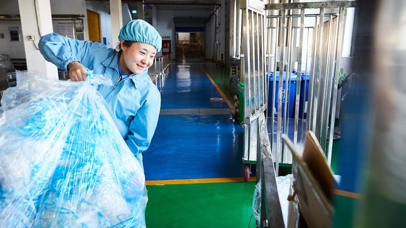 Female factory worker carrying recycling