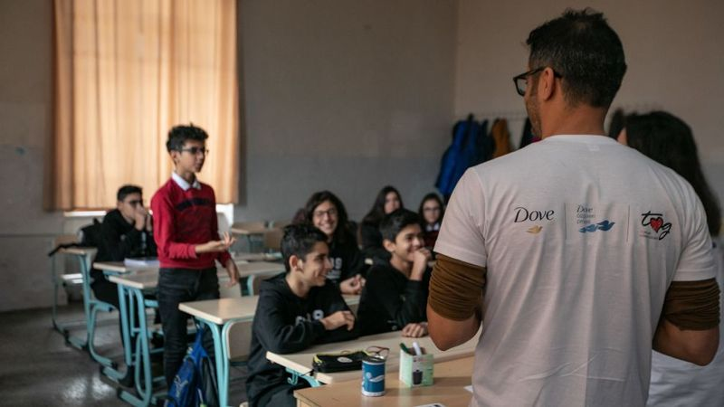 Sınıfta bir öğrenci konuşuyor, onu bir adam dinliyor.