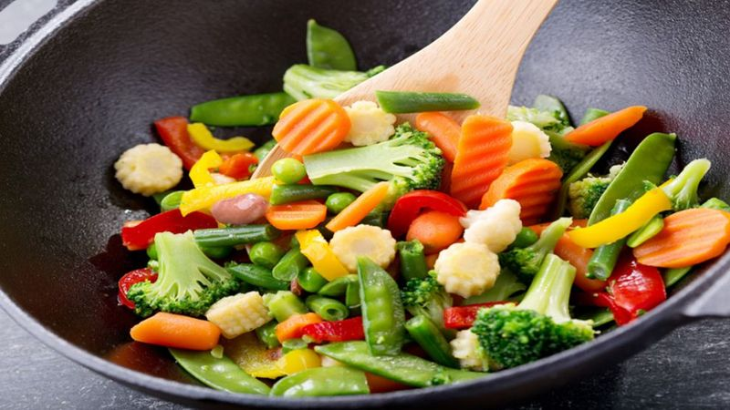 Wok pan with variety of colorful vegetables being stirred