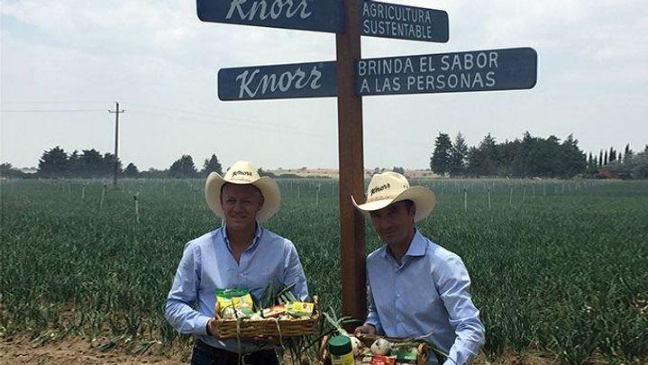 Dos personas con un campo detrás y carteles de Knorr