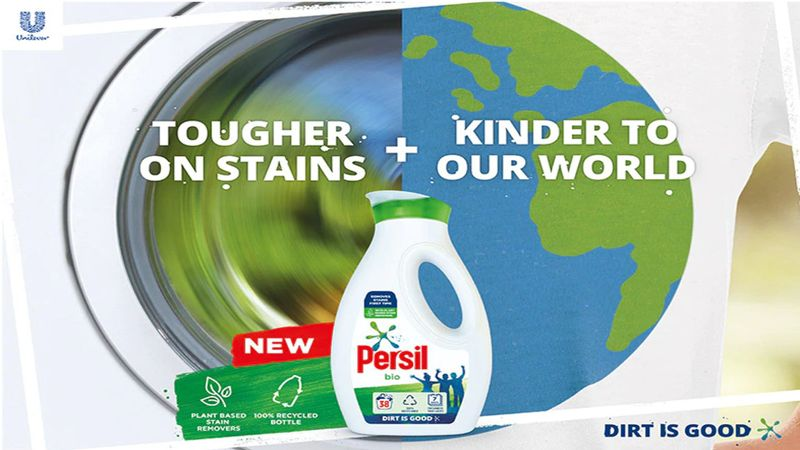 A bottle of Persil in front of a washing machine