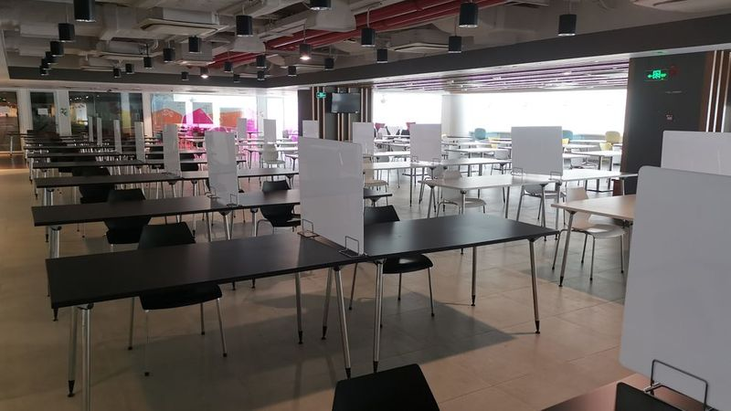 The office canteen where tables and chair have been separated with dividers between them