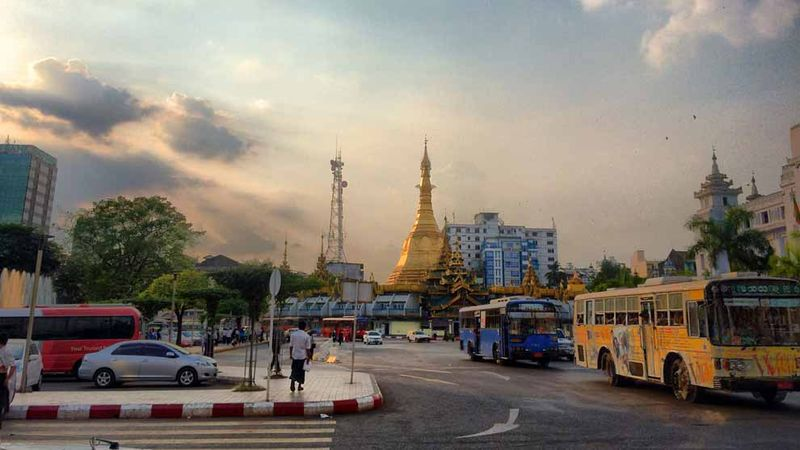 Buses Moving On Road In Front Of Sule Pagoda Against Sky