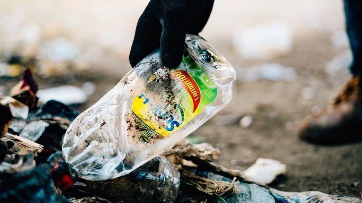 Gloved hand picking up discarded Sunlight plastic bottle from the ground for it to be collected and recycled.
